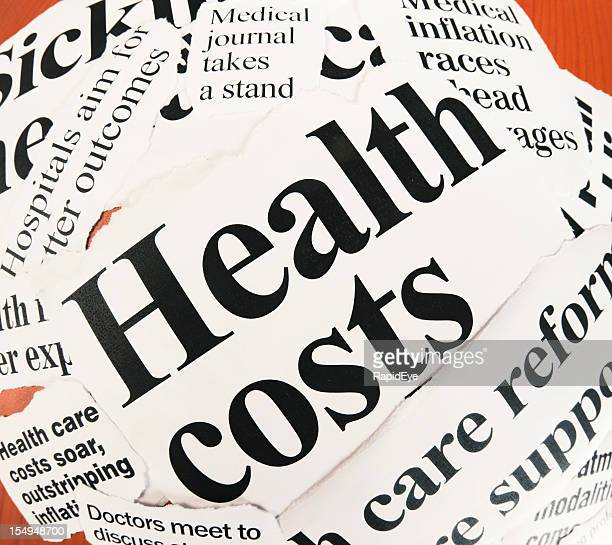 Pile of press headlines on health costs shot with fisheye
