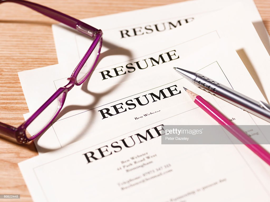 pile of resumes with glasses and pen stock photo