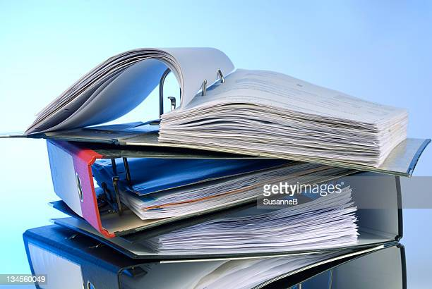 Pile of ring binders with open binder on top