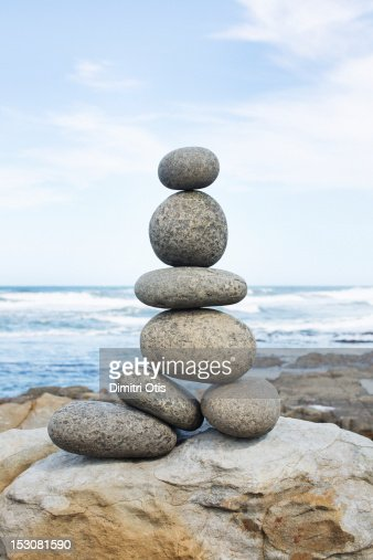 A pile of rocks balancing, sea in background : Stock Photo