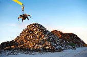 Pile of scrap metal with crane