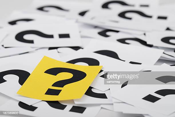 A pile of sheets of paper with question marks on them