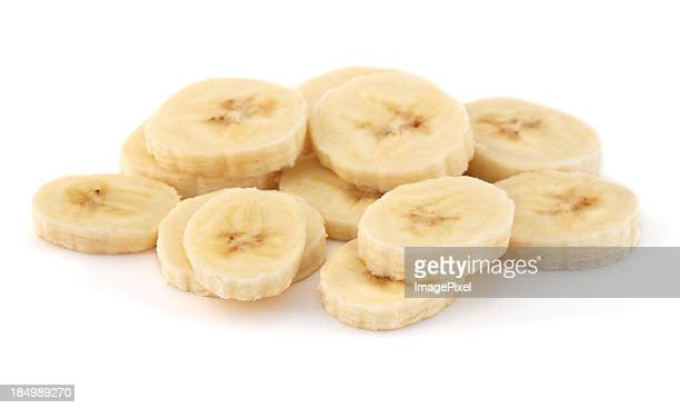 A pile of sliced ripe bananas on a white background