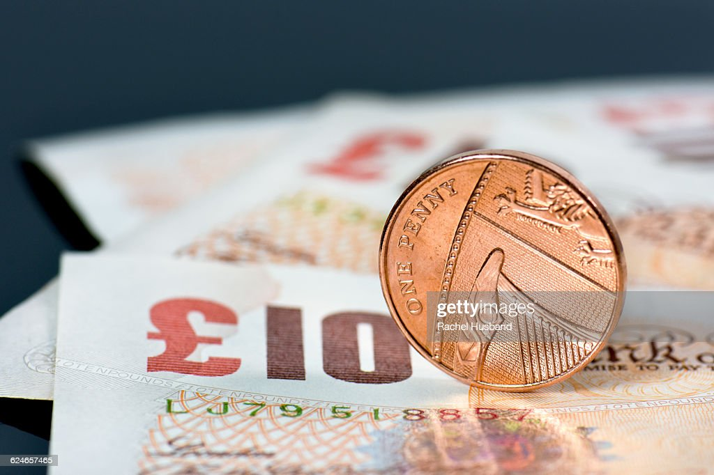 Pile of ten pound Sterling notes and one penny