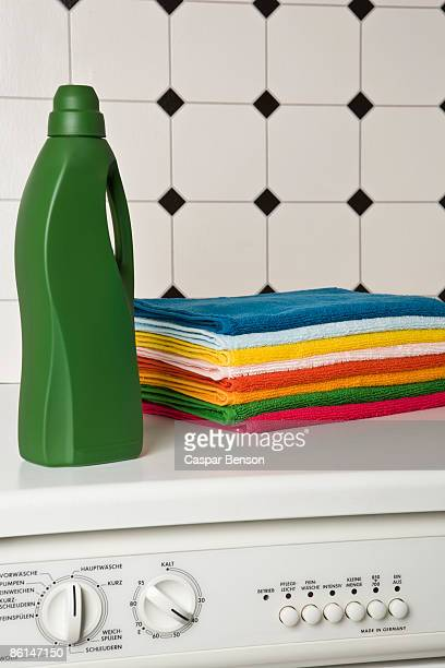 A pile of towels and a bottle of detergent on top of a washing machine