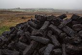 Pile of cut turf waiting to dry, in misty Irish countryside