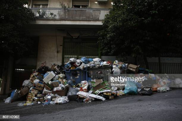 A pile of uncollected garbage sits on a city sidewalk beneath residential apartments during a refuse collection strike by municipal workers in Athens...