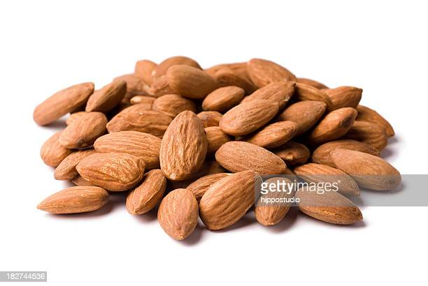 A pile of unpeeled almonds on a white background