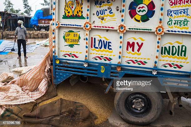 A pile of wheat sits covered with tarps to protect the grain from unseasonal rain next to a truck decorated with the words 'I Love My India' at the...