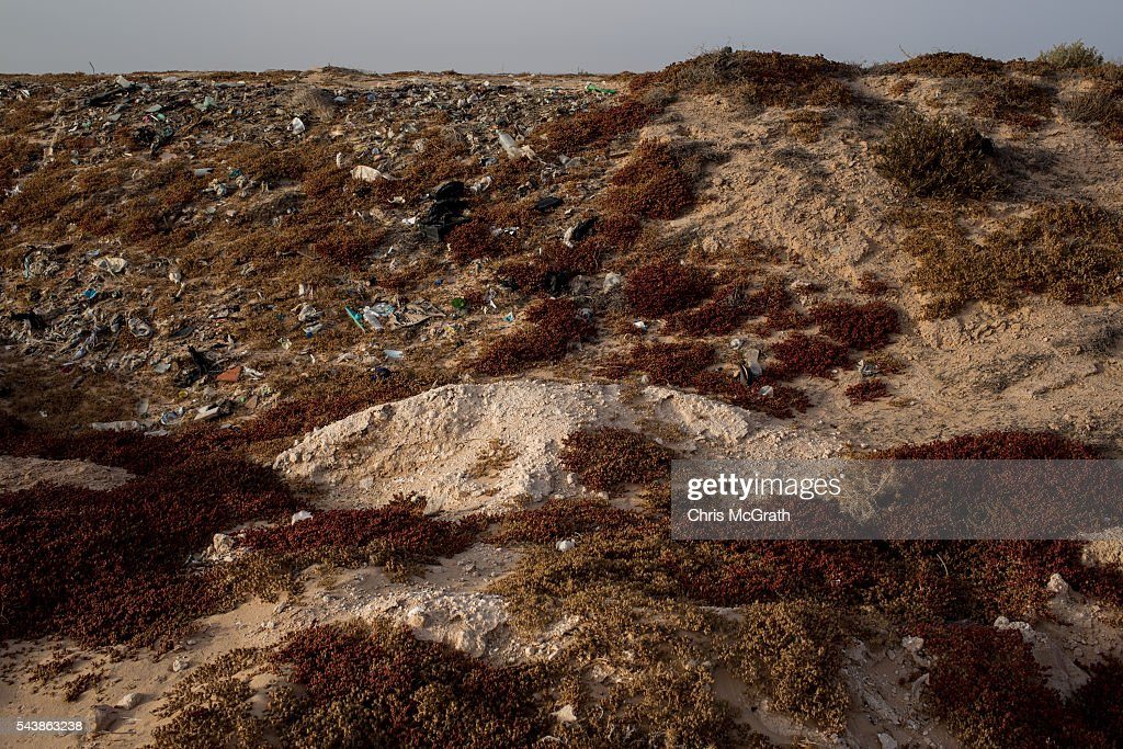 A pile of white soil (center) identifies an unmarked grave of a migrant in a makeshift graveyard on the edges of a salt flat on June 30, 2016 in Zarzis, Tunisia. The makeshift cemetary has an estimated 30 migrants buried in unmarked graves. Since 2012, the Tunisian border town of Zarzis has dealt with the overflow of migrants from Libya. In 2015 with pressure from EU nations, Tunisia tightened its border security with Libya, cutting the number of migrants arriving in Tunisian border towns. Local fishermen from the Zarzis port who were trained in rescue techniques by MSF in 2015 after being involved in weekly rescues, have seen no rescues so far in 2016, primarily due to an increase in rescue boats from international NGOÕs, coastguards and military vessels patrolling the waters off the Libyan coast. However with an estimated 800,000 migrants waiting in Libya to attempt the dangerous crossing to Europe, preparations were made for an expected increase in rescues and arrivals to Tunisia ahead of the 2016 peak season