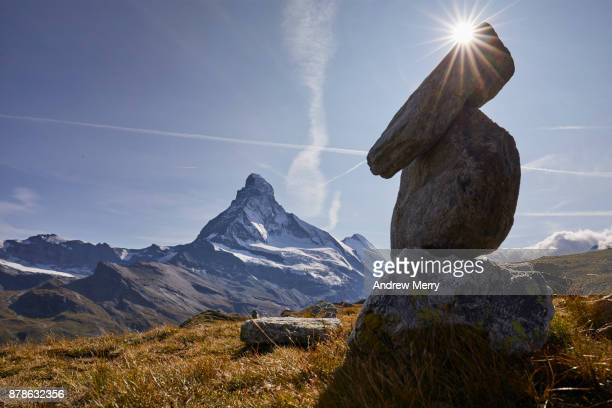 A pile or stack of rocks (cairn). The Matterhorn in the background with sun behind the cairn.