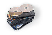 A pile of DVD cases with DVDs on top