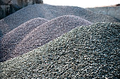 gravel gray stone textures asphalt mix concrete in road construction. Pile rock and stone for Industrial. Piles of bright fine gravel against clear blue sky; Supplier of aggregates and construction ma
