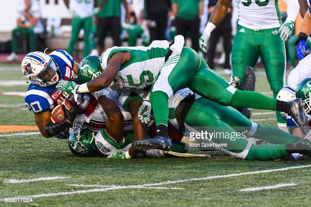 Pile up while Montreal Alouettes running back Tyrell Sutton keeps possession of the ball during the Saskatchewan Roughriders versus the Montreal...