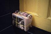 Piled Newspaper Next to Door, Close Up, High Angel View