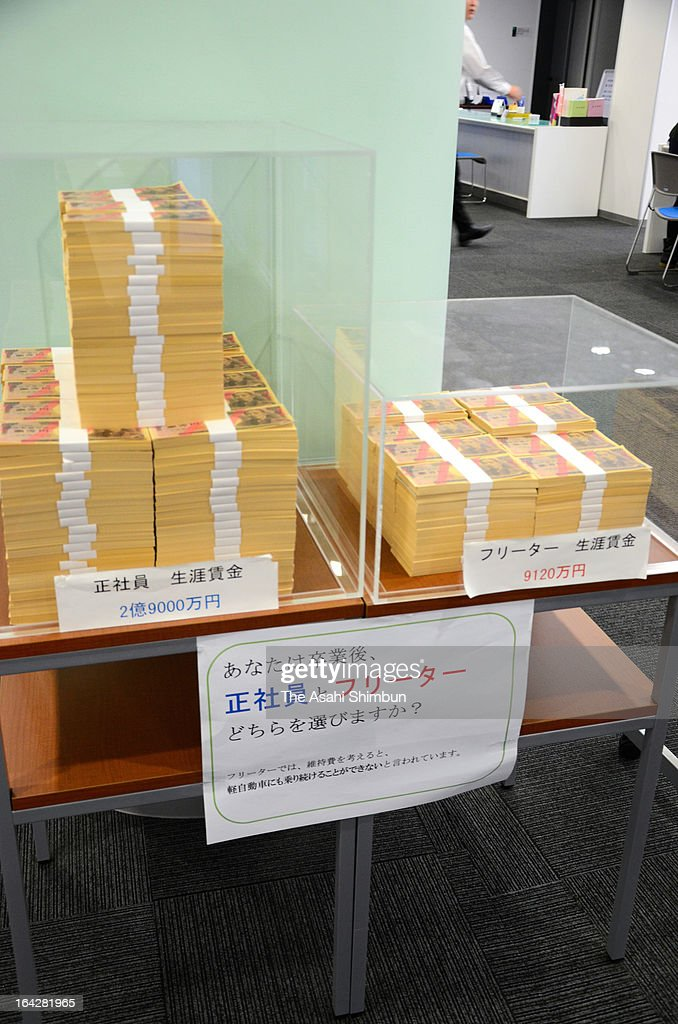Piles of bills comparing the average life-time earnings of freeters' (R) to those of full-time employees'(L) are displayed at the student career support center of Kyushu Sangyo University on November 18, 2011 in Fukuoka, Japan.