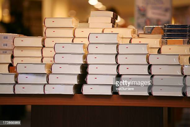 Piles of books on a table in a bookstore