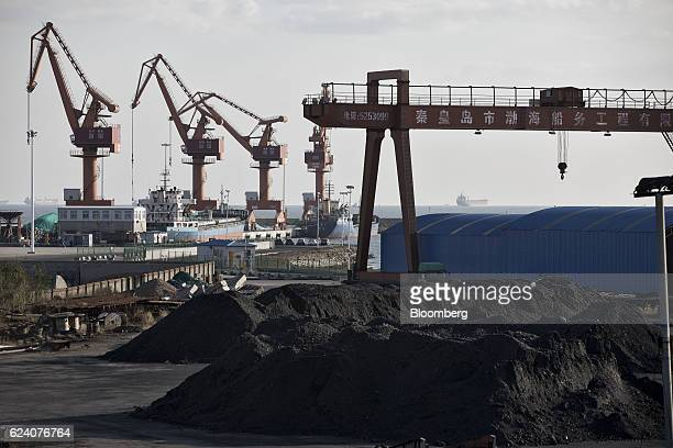 Piles of coal sit near port facilities as gantry cranes stand in the background at the Qinhuangdao Port in Qinhuangdao China on Friday Oct 28 2016...