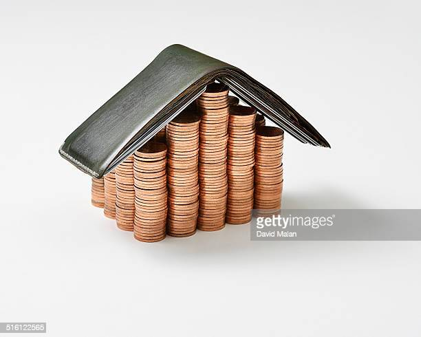 Piles of coins with a wallet resembling a house