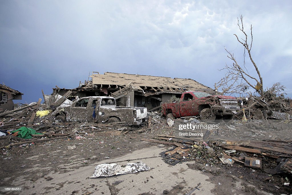 Piles of debris and cars lie around a home destroyed by a tornado May 21, 2013 in Moore, Oklahoma. The town reported a tornado of at least EF4 strength and two miles wide that touched down yesterday killing at least 24 people and leveling everything in its path. U.S. President Barack Obama promised federal aid to supplement state and local recovery efforts.