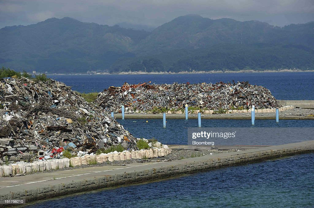 Piles of debris stand at a port in Otsuchi Town, Iwate Prefecture, Japan, on Saturday, Sept. 8, 2012. Japan's economy expanded in the second quarter at half the pace the government initially estimated, underscoring the risk of a contraction as Europe's debt crisis caps exports.Photographer: Akio Kon/Bloomberg via Getty Images
