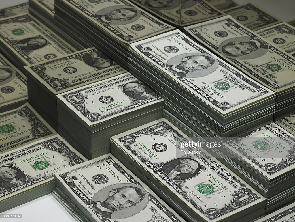 piles of dollar bills reflected in glass : Stock Photo