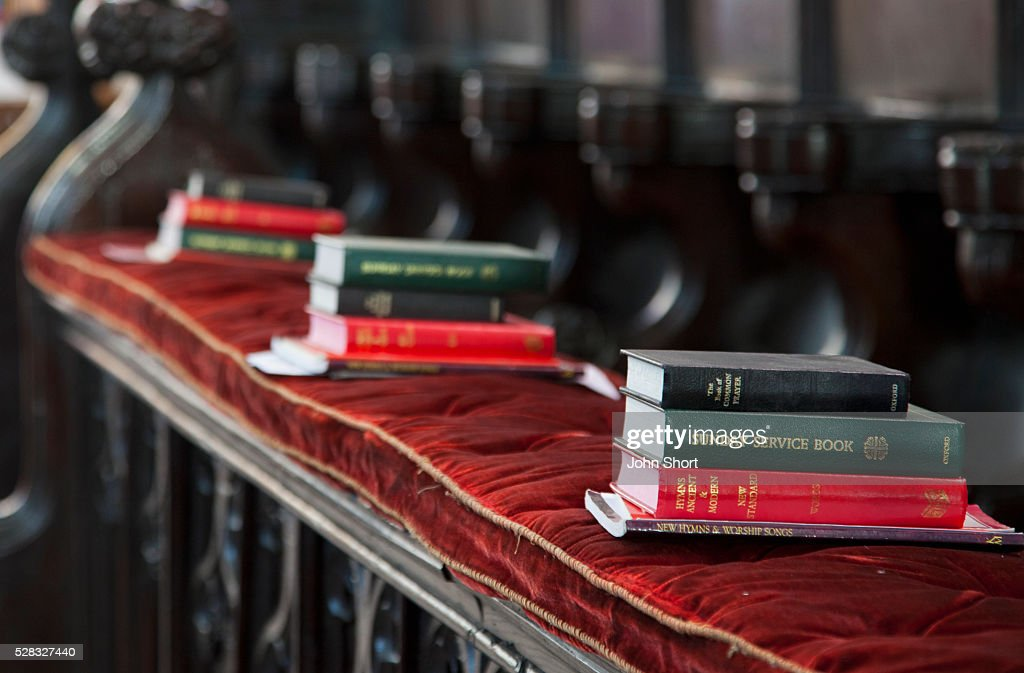 Piles of hymn and service books on a bench in a church; staindrop durham england