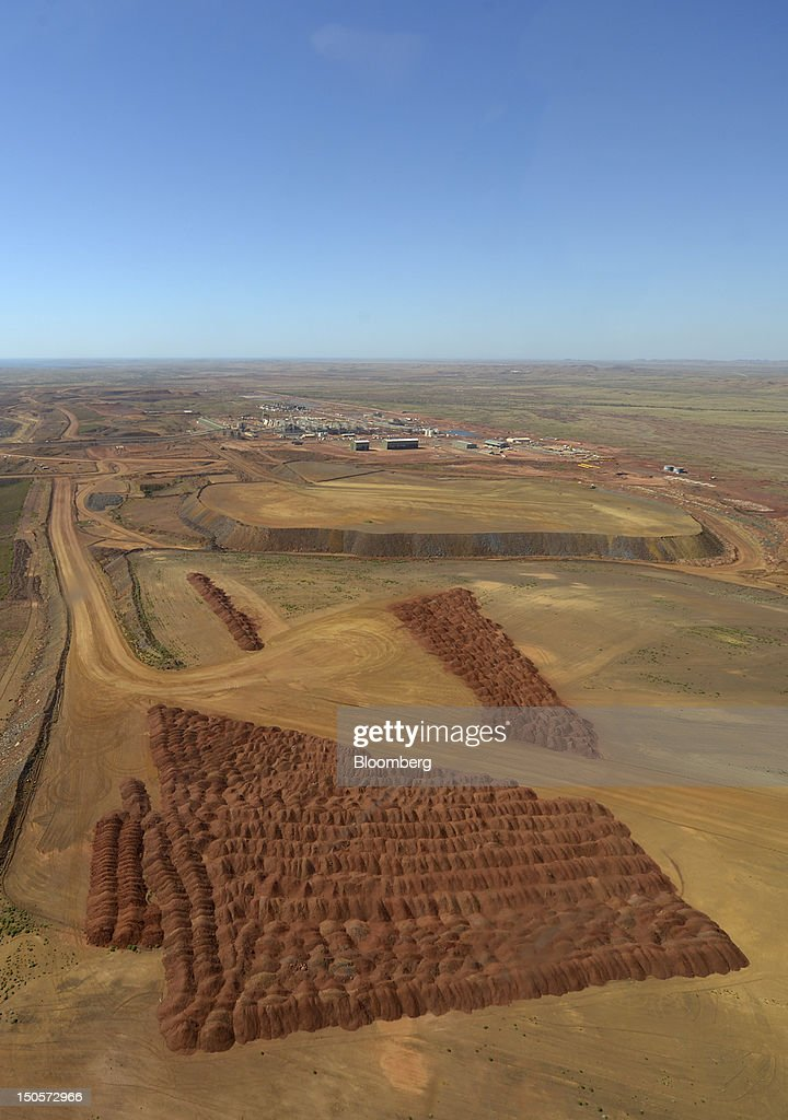 Piles of ore, foreground, are laid out at Citic Pacific Ltd.'s Sino Iron project as the facilities stand under construction in this aerial photograph taken over Karratha, Western Australia, on Monday, Aug. 20, 2012. Australian mining tycoon Clive Palmer expects to receive $500 million a year in royalties from Citic Pacific's $8 billion iron ore mine in Western Australia once it reaches full production. Photographer: Carla Gottgens/Bloomberg via Getty Images