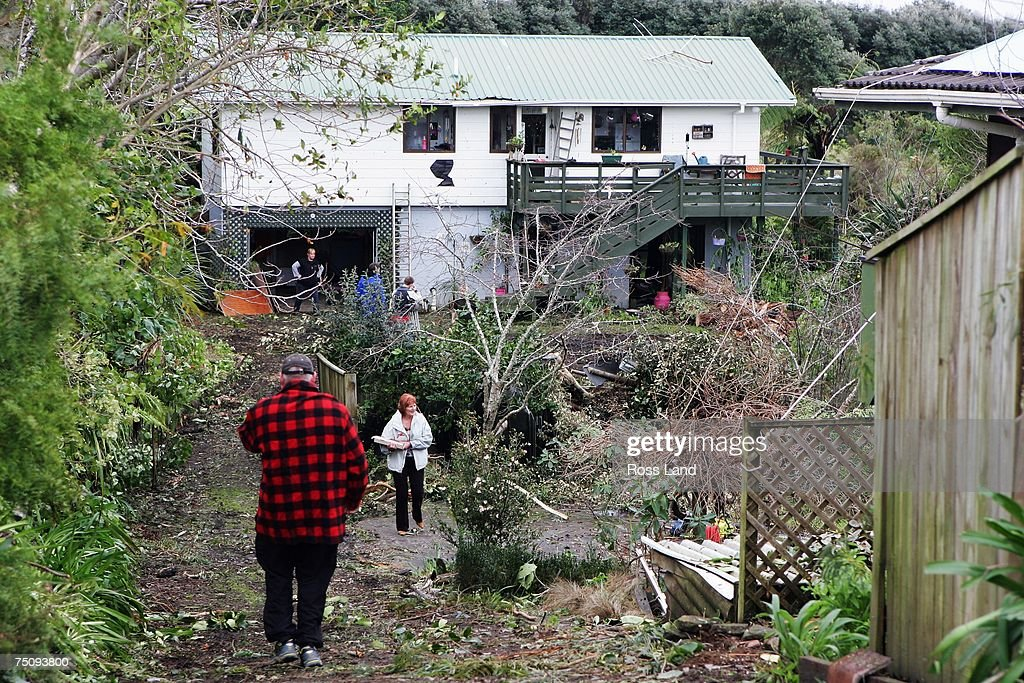 Piles of rubble and damaged trees lie at the front of a property on July 6 2007 in the seaside town of Oakura south west of New Plymouth New Zealand...