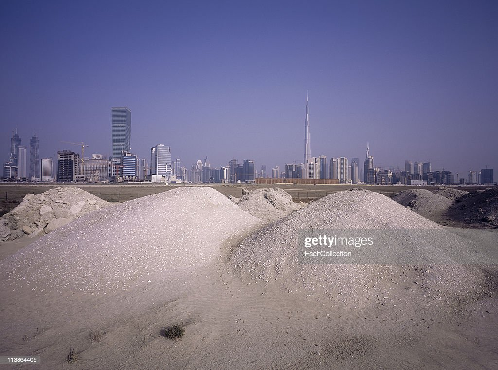 Piles of sand and grit and the Dubai skyline. : Stock Photo