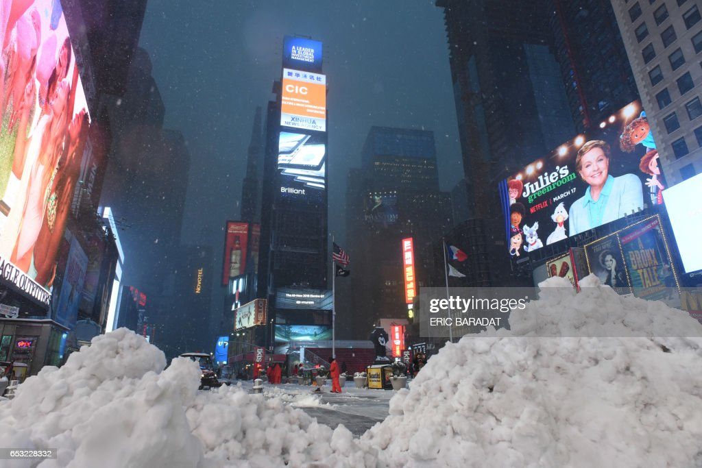 Piles of snow are seen as workers clear the sidewalks in Times Square during a snowstorm in New York on March 14, 2017. Winter Storm Stella dumped snow and sleet Tuesday across the northeastern United States where thousands of flights were canceled and schools closed, but appeared less severe than initially forecast. After daybreak the National Weather Service (NWS) revised down its predicted snow accumulation for the city of New York, saying that the storm had moved across the coast. PHOTO / Eric BARADAT