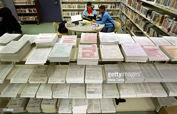Piles of tax forms are seen at the 58th Street Library April 11 2002 in New York City Americans are preparing to beat the upcoming US taxfiling...