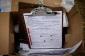 Piles of voter registration forms are fastened to a clip board as Obama Campaign volunteers help to register voters at a weekly farmers market at...