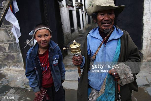 A pilgrim and a child fetch water at the Tashilhunpo Monastery on August 30 2006 in Shigatse of Tibet Autonomous Region China Chinese tourists are...