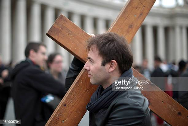 A pilgrim carries a wooden cross after taking part in a stations of the cross ceremony in St Peter's Square on March 29 2013 in Vatican City Vatican