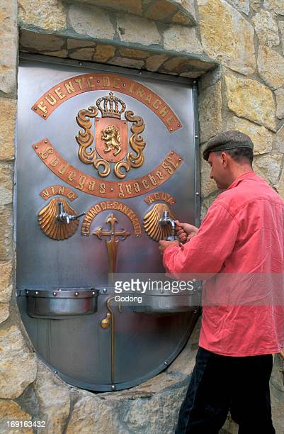 Pilgrim drinking wine at the Irache water and Rioja wine fountain on the Camino de Santiago