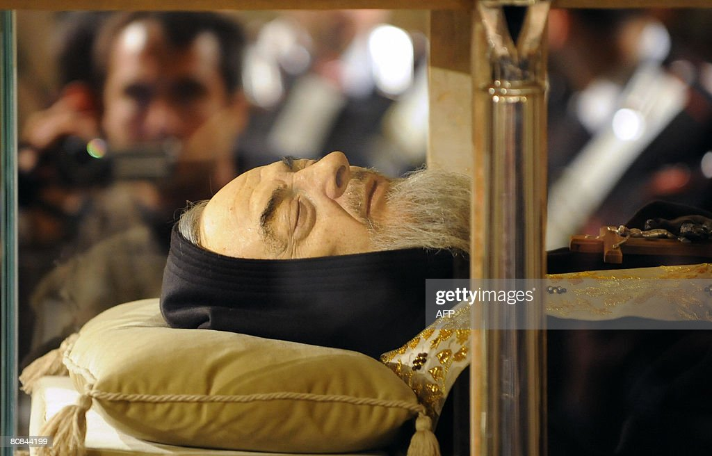 A pilgrim films the body of Padre Pio in a part-glass coffin in the crypt of the old Church of St. Mary of Grace at San Giovanni Rotondo in the Apulia region in southern Italy on April 24, 2008. The Italian saint is a cult figure for millions around the world as many Christians believe had permanent sores on his hands similar to the stigmata, or the wounds of Jesus Christ's crucifixion.AFP PHOTO / MARIO LAPORTA