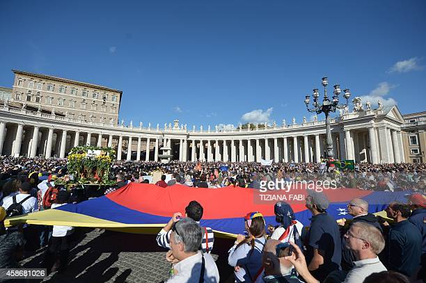 Pilgrim hold a giant Venezuela's national flag as Pope Francis addresses the crowd from the window of the apostolic palace overlooking StPeter's...