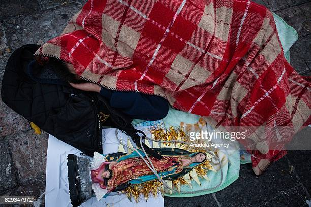 A pilgrim is seen sleeping next to an icon of the Virgin of Guadalupe during the pilgrimade to the Basilica of Guadalupe in the Day of the Virgin of...