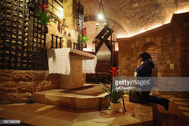 A pilgrim kneels in front of the tomb of Saint Francis of Assisi as she prays during a mass at the Basilica of St Francis of Assisi on March 15 2013...