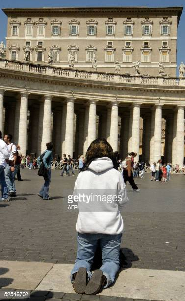 A pilgrim kneels in prayer in St Peter's square at Vatican 1 April 2005 Pope John Paul II received the last rites Thursday evening after suffering a...