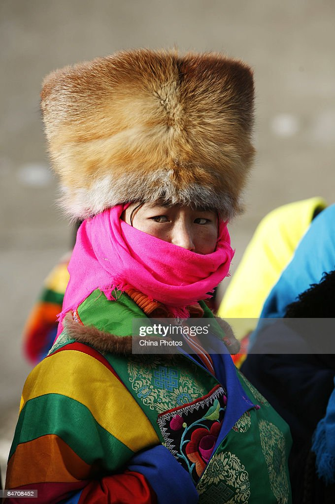 A pilgrim of Tu ethnic minority group attends the 'Tiaoqian' praying ceremony at the Youning Temple on February 8, 2009 in Huzhu County of Qinghai Province, China. The Youning Temple holds the annual 'Tiaoqian' ceremony in the first lunar month each year. During the ceremony, monks will wear colourful traditional clothes and masks, performing the 'Fawang Dance' and 'Horse-headed Warrior Dance' to scare away evil spirits. Pilgrims also pray for good luck during the ceremony.