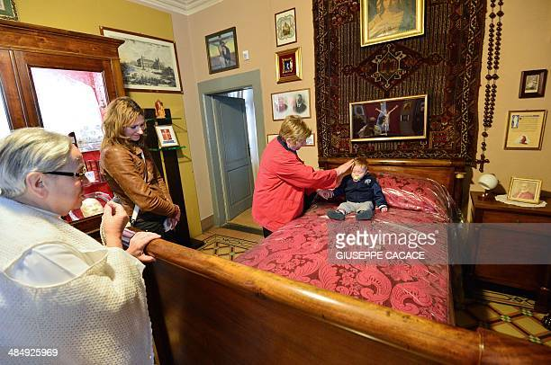 A pilgrim places a child on the bed of late pope John XXIII at the 'Ca Maitino' house where he used to spent his holidays in Sotto il Monte Giovanni...