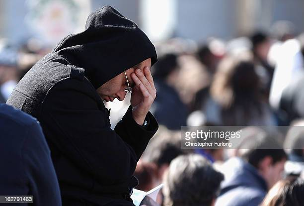A pilgrim prays as he attends Pope Benedict XVI's final general audience in St Peter's Square before his retirement on February 27 2013 in Vatican...