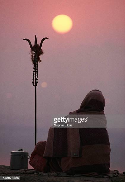 A pilgrim prays near the holy river during the Kumbh Mela festival at sunset
