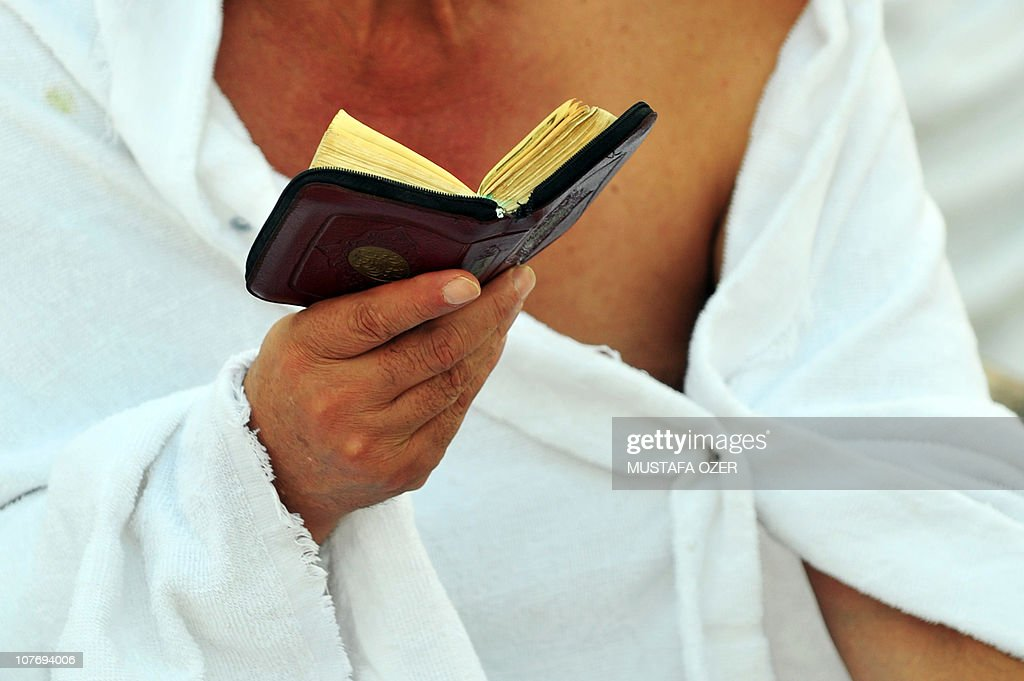 A pilgrim reads the Muslim holy book or Koran in the Mina valley five kilometres east of the Saudi Arabian holy city of Mecca on November 14 as some...