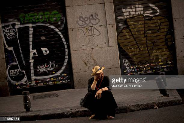 A pilgrim sits as he waits for Pope Benedict XVI's visit in Madrid on August 18 2011 Pope Benedict XVI is heading to Madrid for a millionstrong...