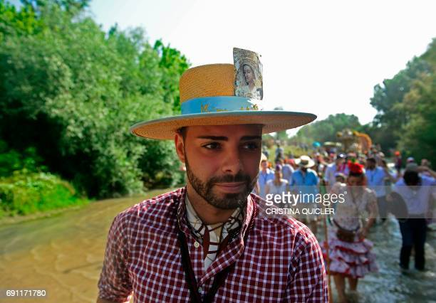 A pilgrim sporting a hat with an image of the Virgin of the Rocio crosses the Quema river during the annual El Rocio pilgrimage in Villamanrique near...