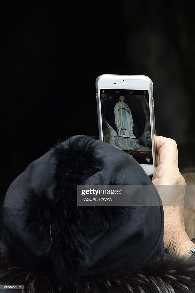 A pilgrim takes a picture of the statue of the Virgin Mary inside the Massabielle grotto on February 11, 2016 for the 158th anniversary of the virgin Mary's apparition to Bernadette Soubirous in Lourdes, Southern France. / AFP / PASCAL PAVANI