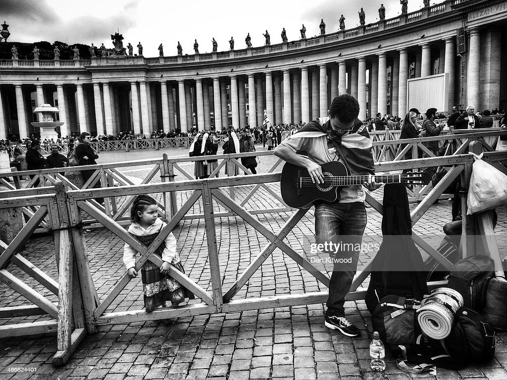 A pilgrim tunes a guitar in St Peter's Square on April 26, 2014 in Vatican City, Vatican. Dignitaries, heads of state and Royals, from Europe and across the World, are gathering in the Vatican ahead of tomorrow's canonisations. The late Pope John Paul II and Pope John XXIII will be canonised on Sunday 27 April, inside the Vatican when 800,000 pilgrims from around the world are expected to attend.
